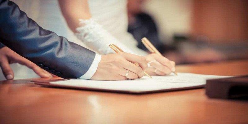 Cô dâu chú rẻ đặt bút ký giấy đăng ký kết hôn